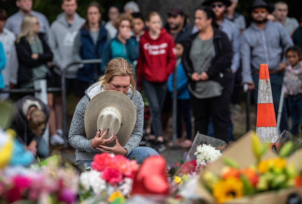 A woman covers her face with a hat after giving a flower to the Arnur mosque that became the scene after a shooting in March in Christchurch, New Zealand