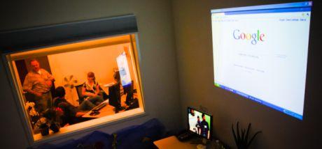 GoogleのJohn Boyd氏(立っている人物)と、ユーザーエクスペリエンスリサーチャーのLaDawn Jentzch氏が、Googleのユーザビリティラボの仕組みを米CNETのTom Krazit記者に説明している様子を観察ルームから見たところ。